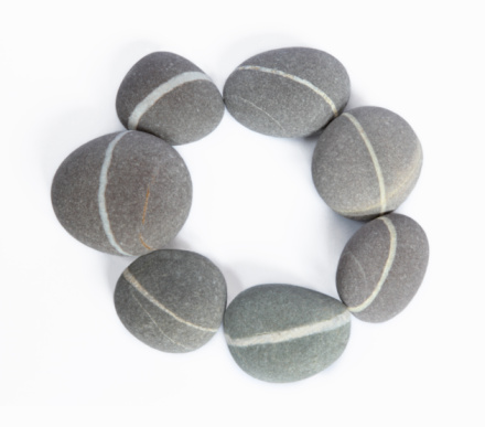 Seven smooth granite pebbles each with a white quartz vein arranged with the quartz veins linking forming a circle, on a white background.